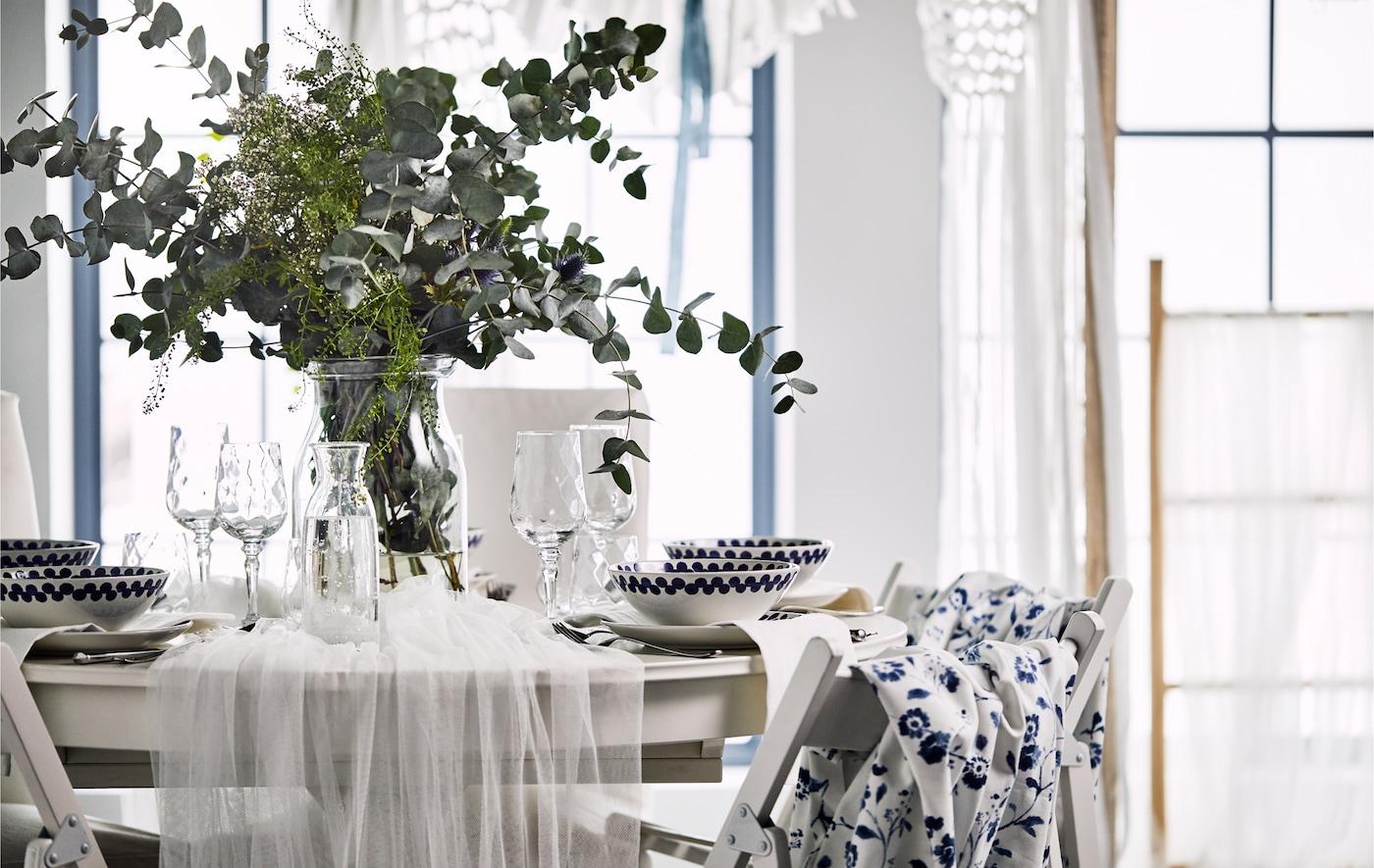 En romantisk borddekking med hvit tyll drapert over et rundt bord og en vase med markblomster og eukalyptusblader.