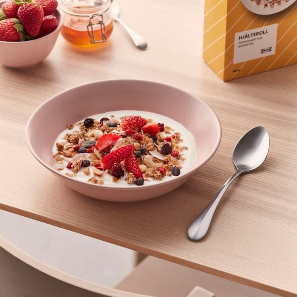 En rosa djup tallrik med yoghurt och granolan HJÄLTEROLL och en sked vid sidan om.