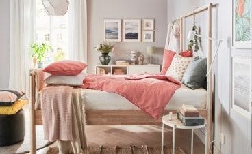 En seng med koralfarvede puder og tæpper i et soveværelse