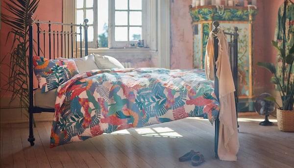 En seng står i et lyst lokale hvor solen strømmer ind. På sengen er der et meget farverigt sengetøj.