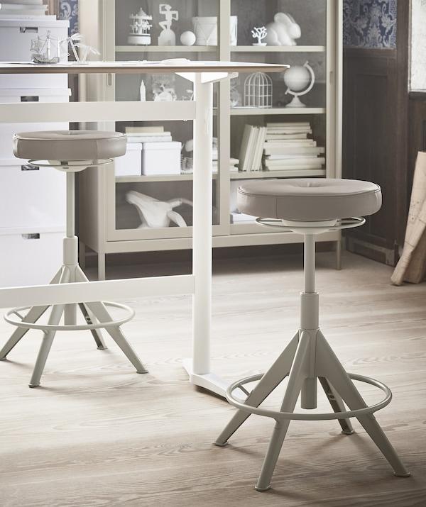 En sitt-/ståskrivbord med två sitt-/ståstöd i beige och ett vitrinskåp i bakgrunden.