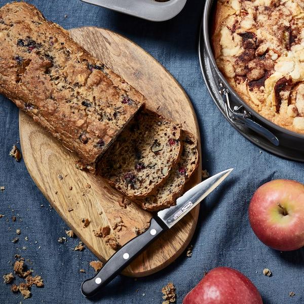 En skærekage ligger på et skærebært. De to første skiver er skåret med kniven, der nu ligger på skærebrættet ved siden af to røde æbler.
