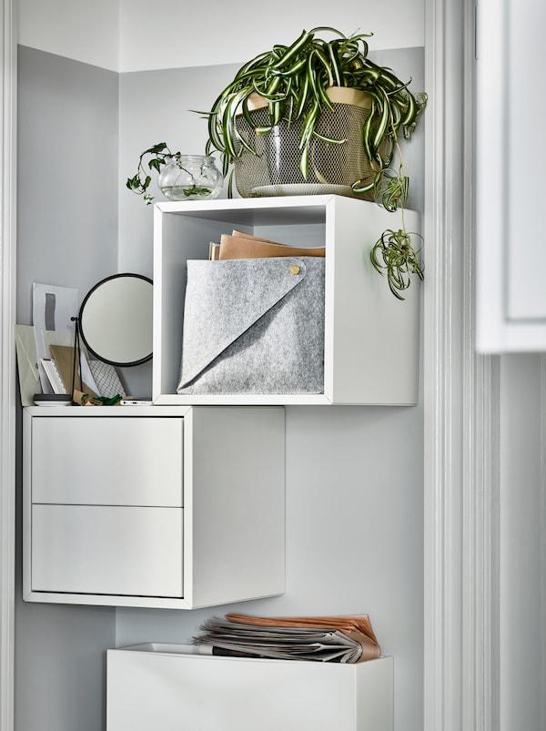 En smal væg ved siden af en dør med hvide, vægmonterede EKET skabe. Et skab er åbent med en plante ovenpå, det andet er med skuffer.