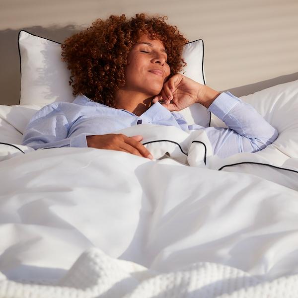 En smilende kvinde med krøllet hår ligger i en seng med tre puder med hvide pudebetræk og en hvid dyne.