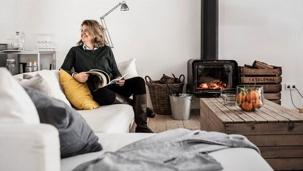 En smilende kvinne sitter i sofaen i stua si og leser et blad.