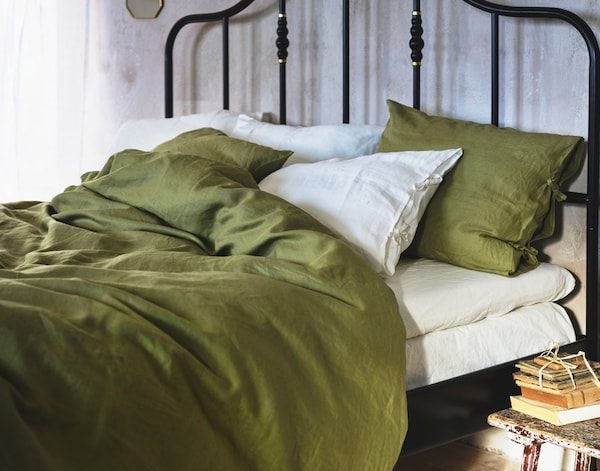 En sort seng af metal med hvide lagner, hvide hovedpuder, grønner hovedpuder og grønt dynebetræk.
