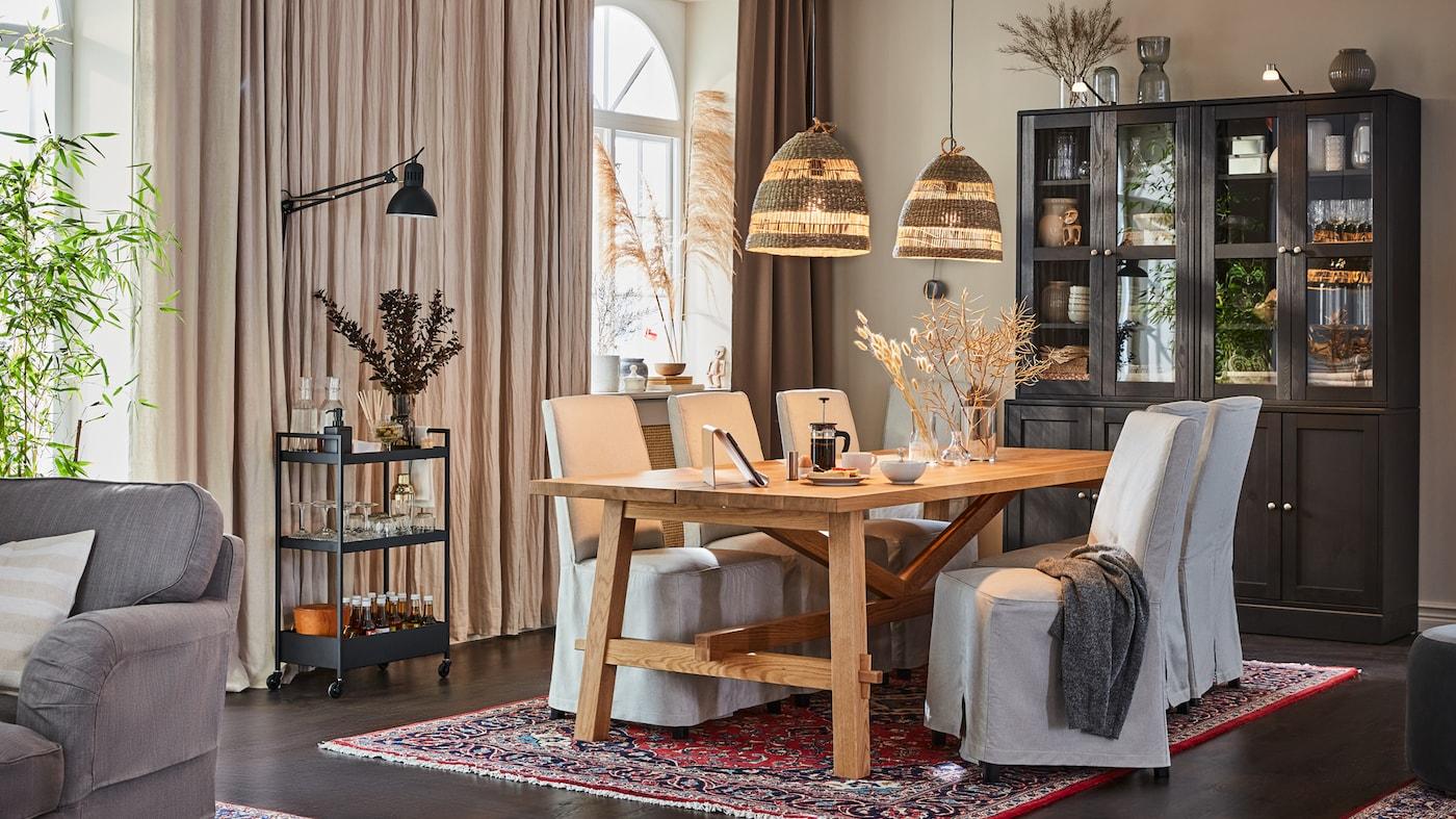 En spisestue med et bord i træ og fire stole med betræk i lyst stof. Over bordet hænger to lamper lavet søgræs. For enden står to vitrineskabe i mørkt træ.