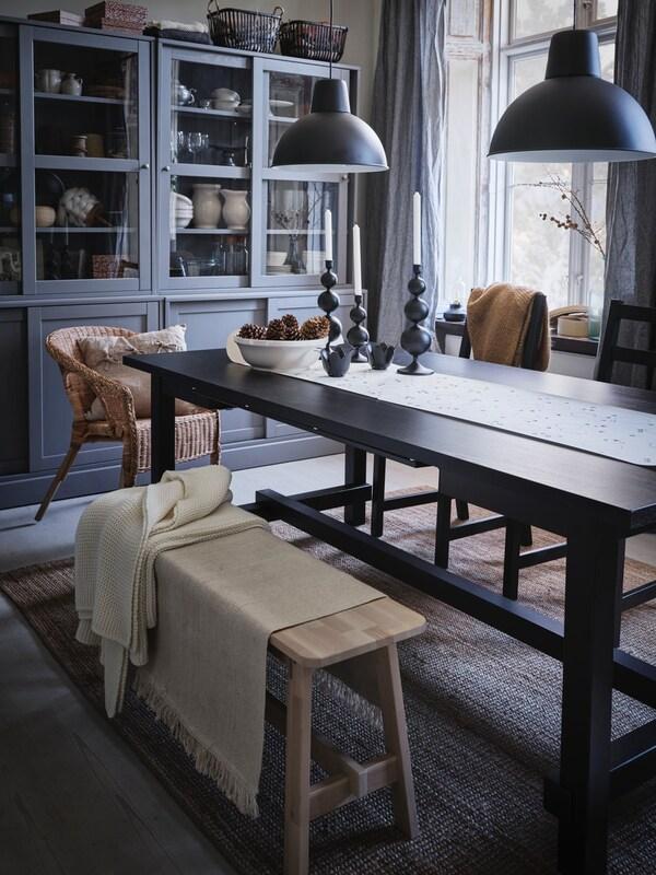 En spisestue med et mørkt spisebord, et gråt vitrineskab op af væggen og en bænk i forgrunden.
