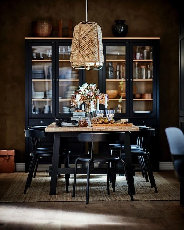 En spisestue med et spisebord i midten og sorte stole rundt om. Fra loftet hænger en bambuslampe og op af væggen i baggrunden står et sort vitrineskab.