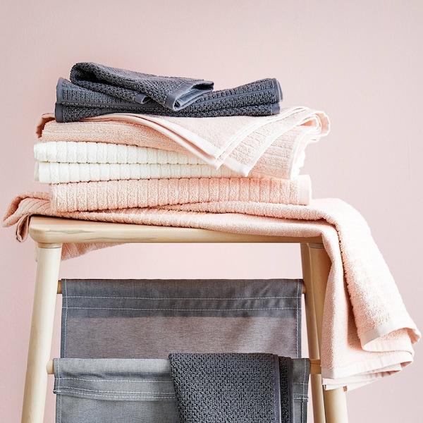 En stak grå, rosa og hvide håndklæder ligger i en bunke på en taburet af træ.