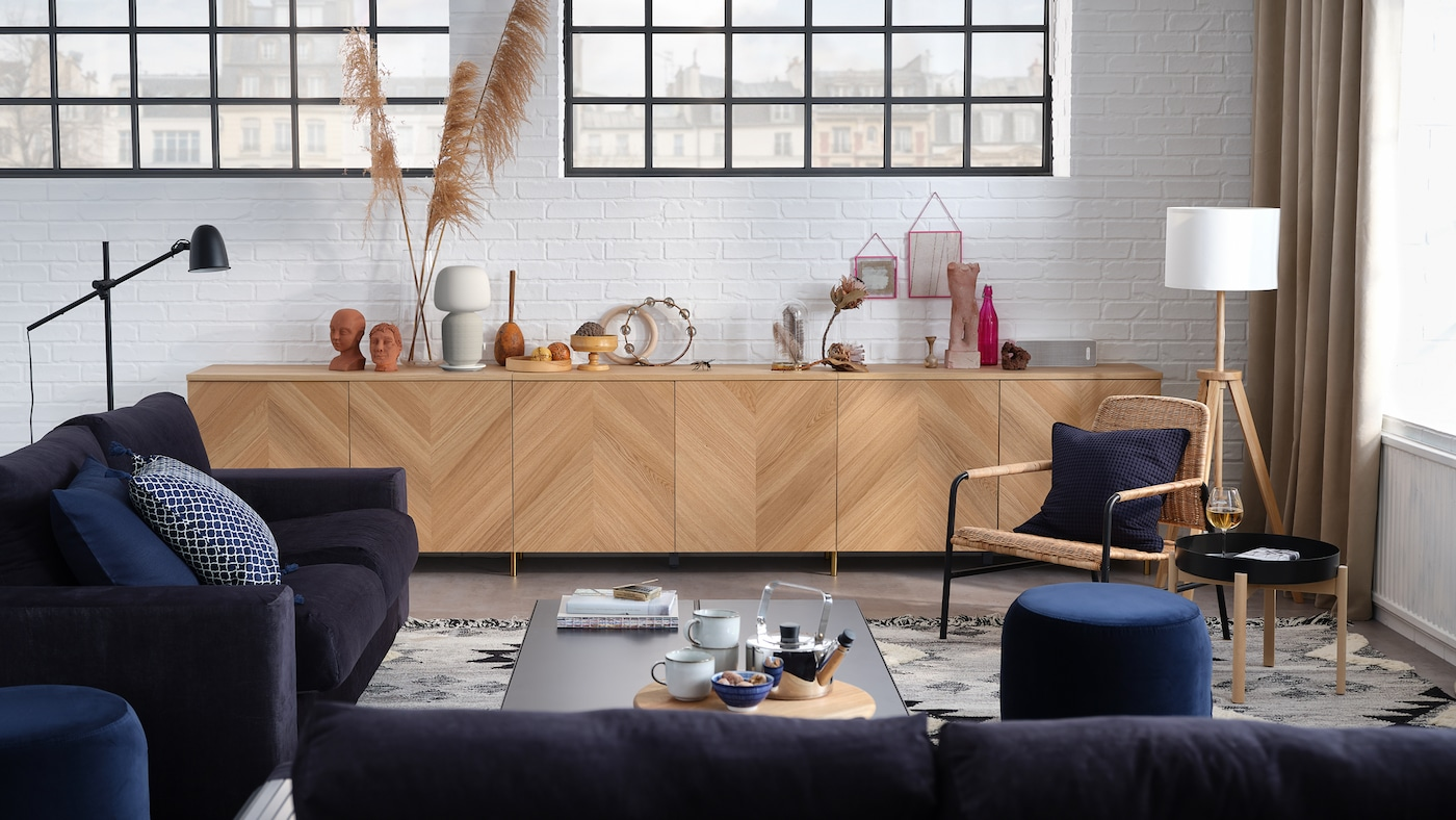 En stilfuld stue med en 3-pers. sofa, en 2-pers. sovesofa, en opbevaringskombination med låger og en lænestol.