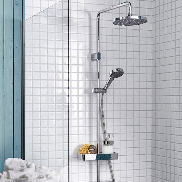 En stor bruser med en lille håndbruser i et badeværelse med små gråhvide fliser.
