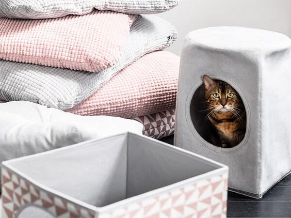 En stribet kat kigger ud af et gråt LURVIG kattehus omgivet af bløde, lyserøde, grå og mønstrede puder.