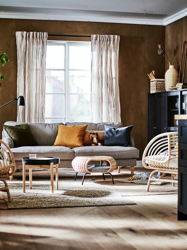 En stue med brune vægge, en grå sofa og møbler i naturmaterialer