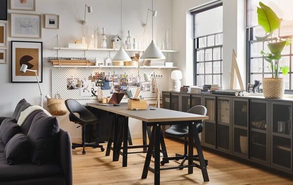 En stue med et stort skrivebord, der også kan bruges som spisebord og en masse IVAR opbevaringsskabe.