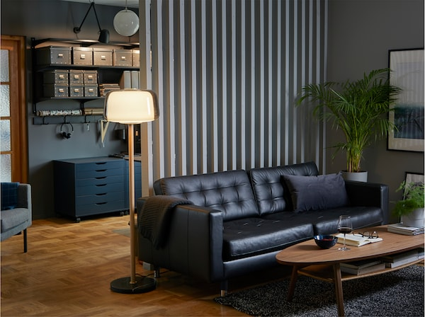 En svart LANDSKRONA 3-sitssoffa i narvläder, ett soffbord och en lampa i ett behagligt, färgkoordinerat hemmakontor.