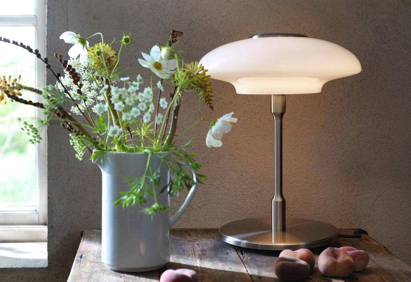 En TÄLLBYN bordlampe ved siden af en buket blomster.