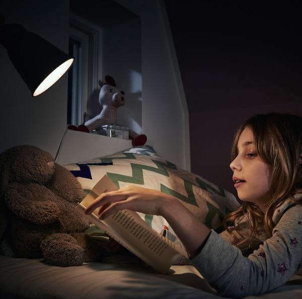 En teenager ligger på sin seng og laver lektier ved siden af en sengelampe med en RYET LED-pære.