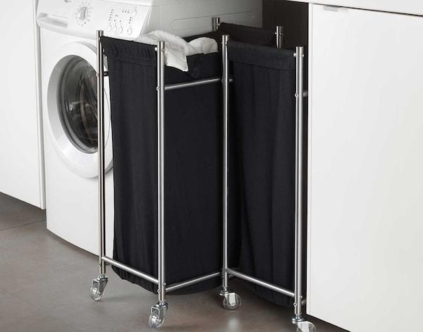En tøjkurv fyldt med vasketøj, der står i et bryggers .