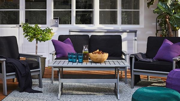 En topersoners sofa og to lænestole af træ med mørke hynder står rundt om et havebord i samme stil (BONDHOLMEN serien) på en terrasse.
