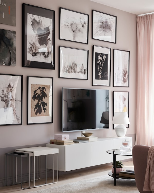 En traditionell vardagsrumsvägg, full av bilder med KNOPPÄNG ramar i svart, bakom en tv monterad på en låg, vit tv-bänk.