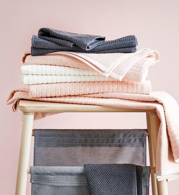 En trætaburet med håndklæder på i lyserød, grå og hvid