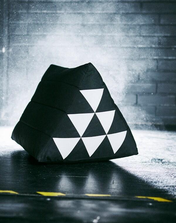 En trekantet SAMMANKOPPLA pude står i et mørkt rum. Det hvide mønster af trekanter på siden reflekterer kameraets blitz.