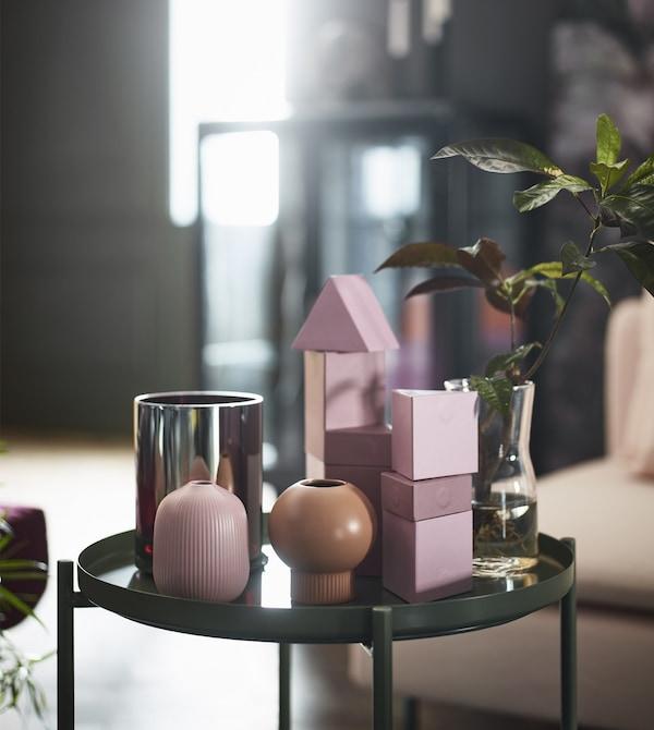 En una mesa con bandeja verde, dos floreros GRADVIS redondos de cerámica de color rosa y natural.