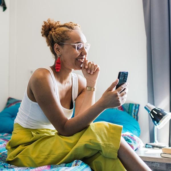 En ung kvinde sidder på sin seng med sin telefon i hånden. Hun har gule bukser på.