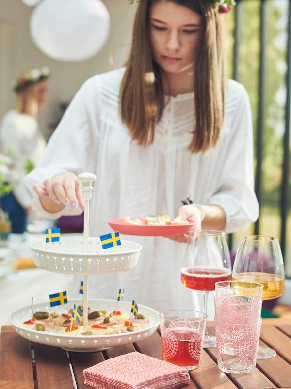 En ung kvinne forsyner seg fra et GARNERA serveringsfat på et bord der det også står fylte DYRGRIP glass.