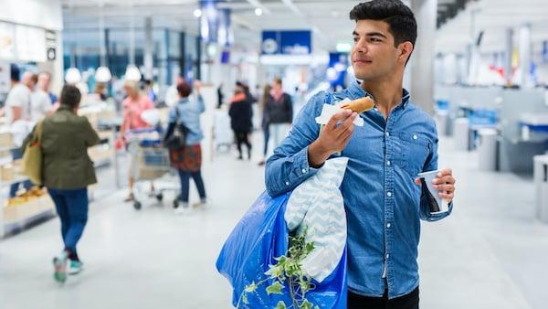 En ung mand står med en blå FRAKTA pose fyldt med varer over skulderen, mens hans spiser en Veggie hotdog inde i et IKEA varehus.
