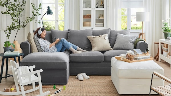 En ung tjej sitter med hörlurar i en soffa och gör anteckningar