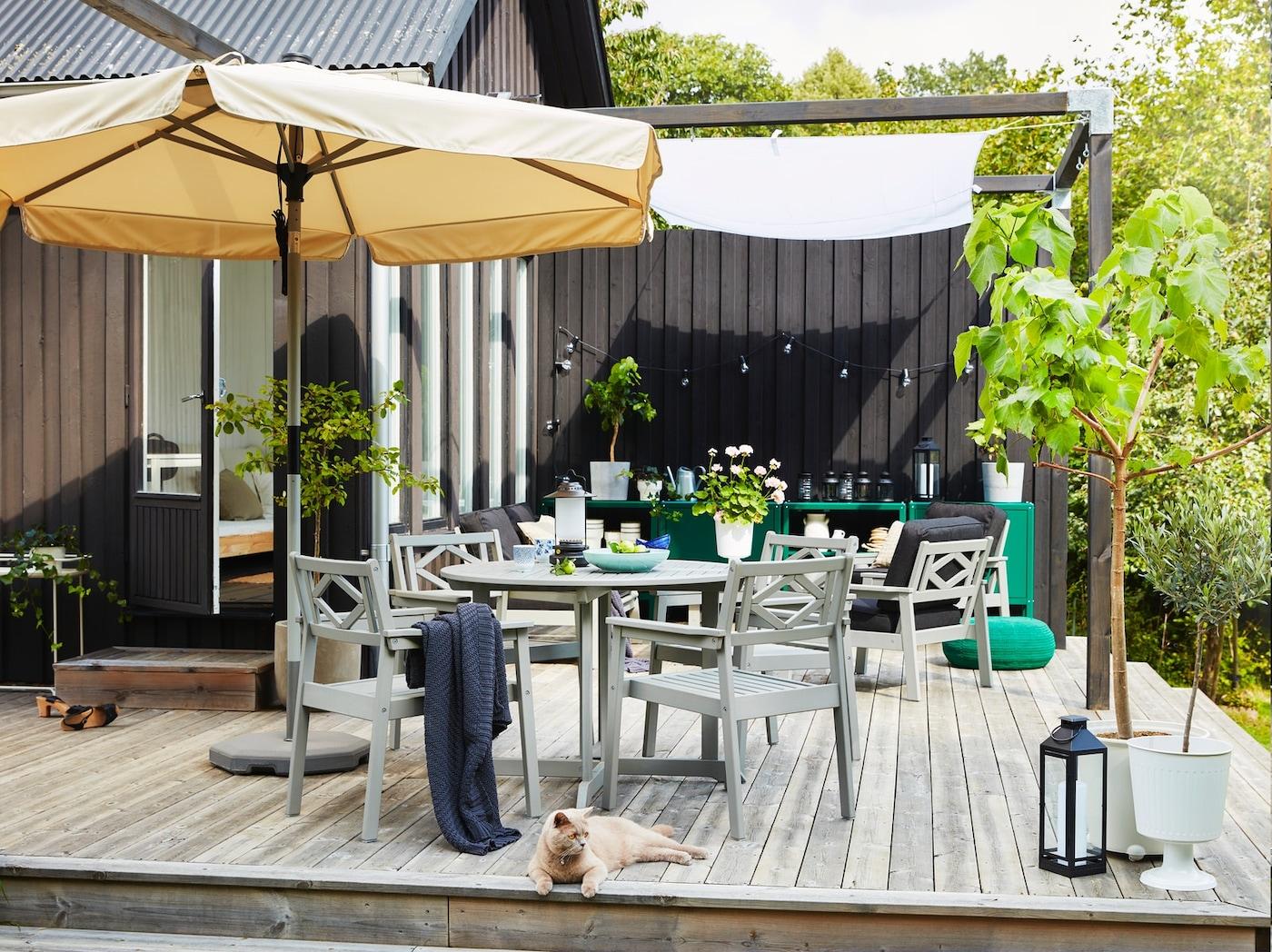 En uteplass på en treplatting med en beige parasoll, grå hagemøbler, grønne plantede trær og en katt.