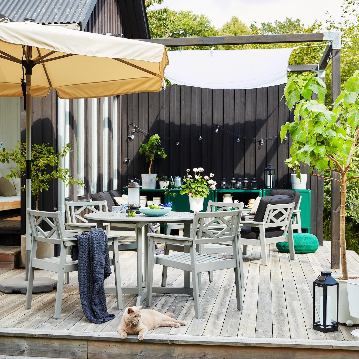En uteplass på en treplatting med en beige parasoll, grå hagemøbler, grønne plantede trær og en grå og oransje katt.