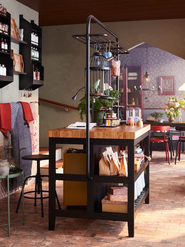 En VADHOLMA köksö och KULLABERG barpall används som reception, med väggexponering av produkter som finns till försäljning.