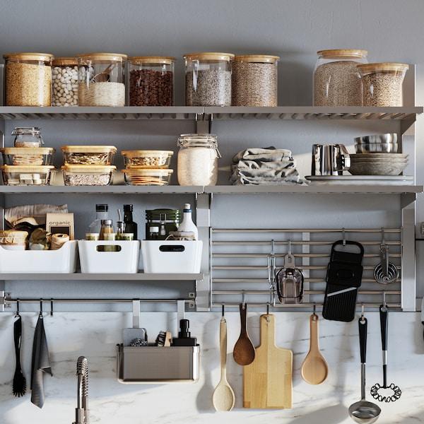 En vægmonteret KUNGSFORS køkkenopbevaringsserie med glaskrukker med låg, hvide VARIERA opbevaringskasser og hængende redskaber.