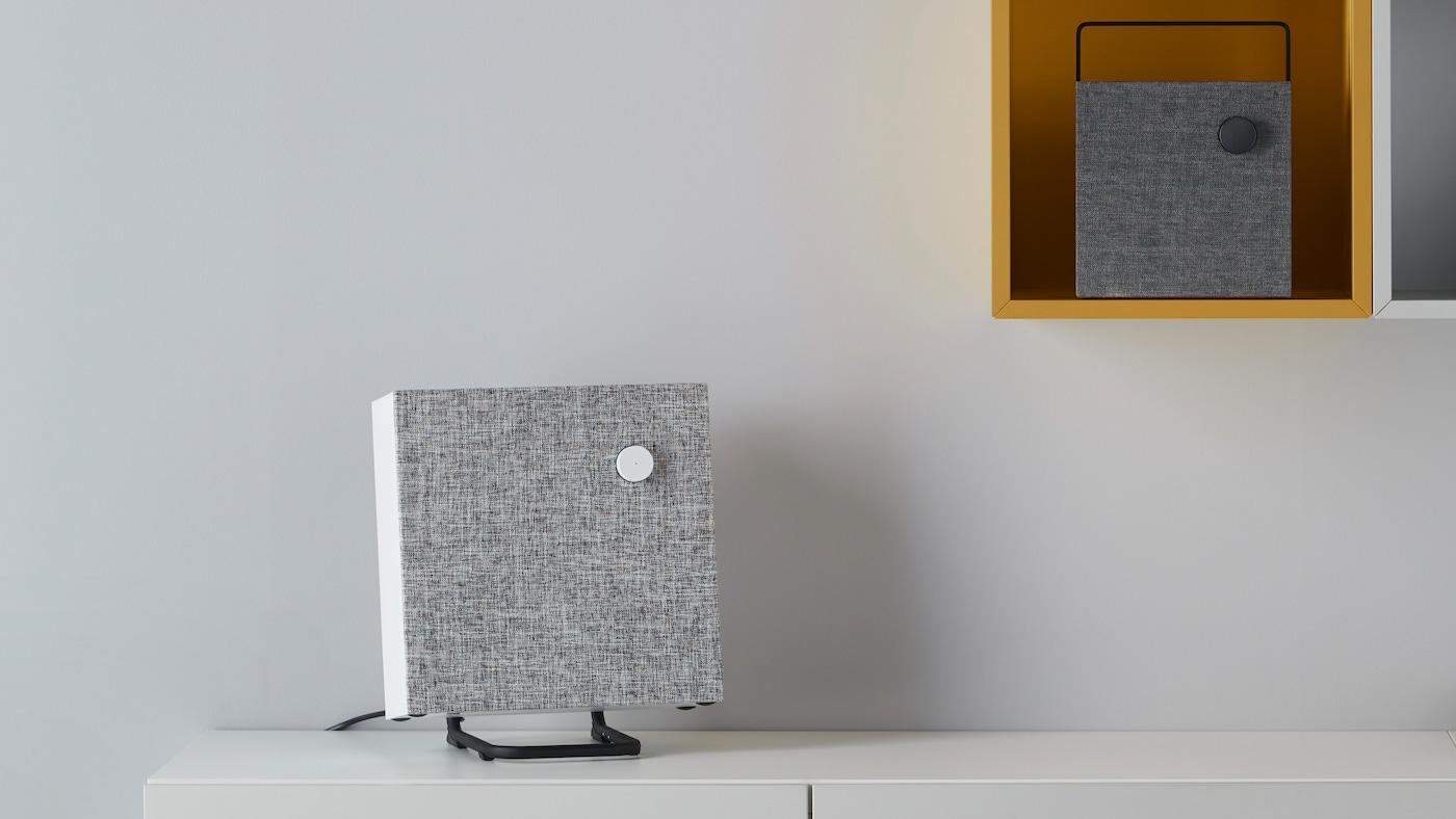 En vit ENEBY högtalare står i ett stativ på en bänk med en vit vägg i bakgrunden.