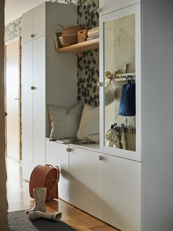 En vit hallkombination skapad av en PLATSA garderob med nio dörrar, med ett utrymme i mitten som används som sittplats.