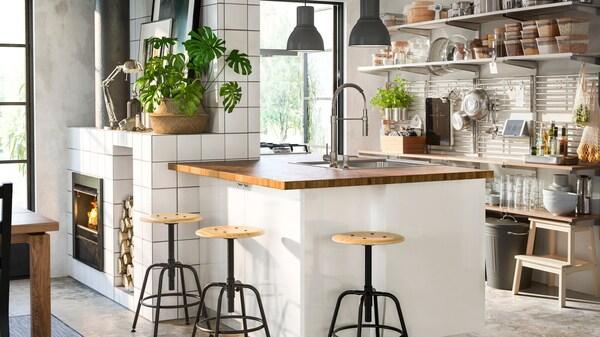 En vit köksö med bänkskiva i trä och tre stycken barpallar placerade runt om, i ena hörnet av rummet syns en braskamin och det är öppna hyllor i köket