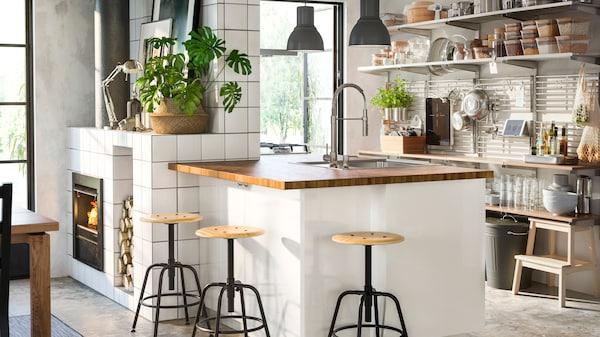 En vit köksö med bänkskiva i trä och tre stycken barpallar placerade runt om, i ena hörnet av rummet syns en braskamin och det är öppna nyllor i köket