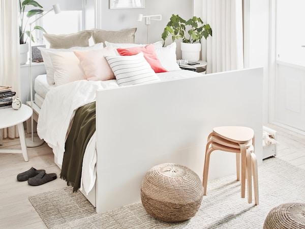 En vit MALM dubbelsäng bäddad med många kuddar och prydnadskuddar med sänggaveln som fotände i ett ljust rum.