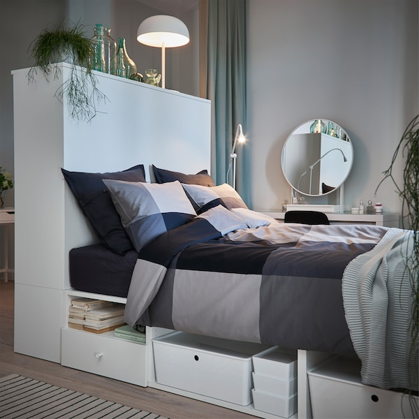 En vit säng med svarta och gråa örngott och påslakan i ett grått och grönt sovrum.