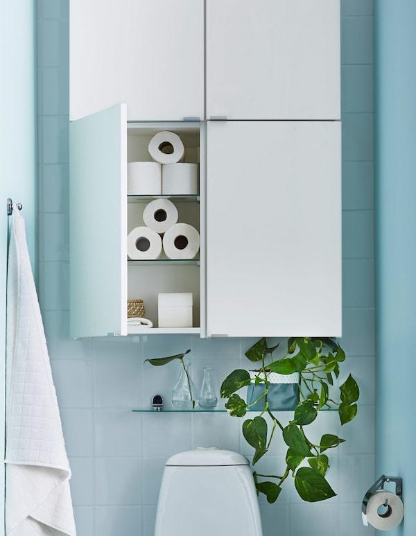 Encima del inodoro hay cuatro armarios blancos sencillos y una pequeña balda de vidrio con plantas.