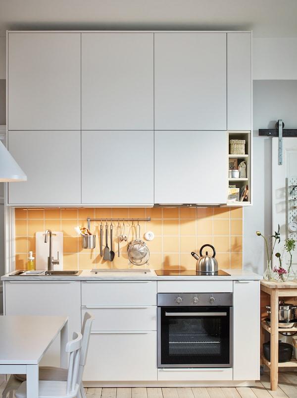 Encimera de cocina con fregadero, vitrocerámica y menaje enmarcado arriba y abajo con filas de armarios METOD con frente blanco.