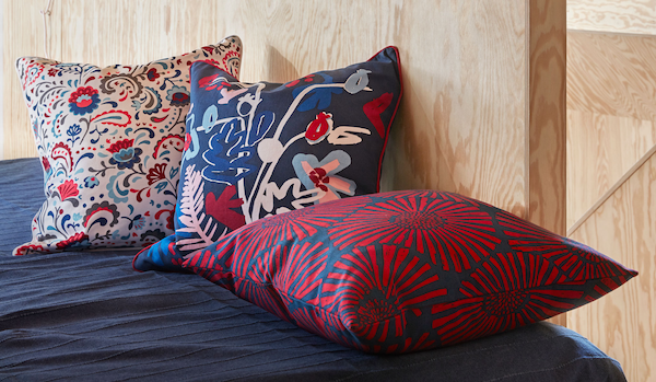 End or side of a made bed by a plywood-panelled wall. Three richly patterned cushions decorate the bed.