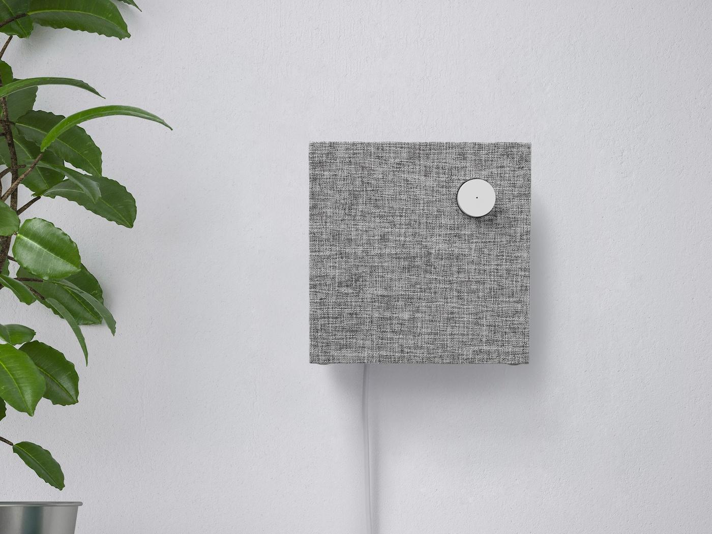 ENEBY Bluetooth zvučnik postavljen na zid na bijeloj polici pokraj zelene biljke.