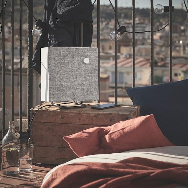ENEBY Lautsprehcer in weiß auf einer Terrasse mit einer Stadt im Hintergrund.