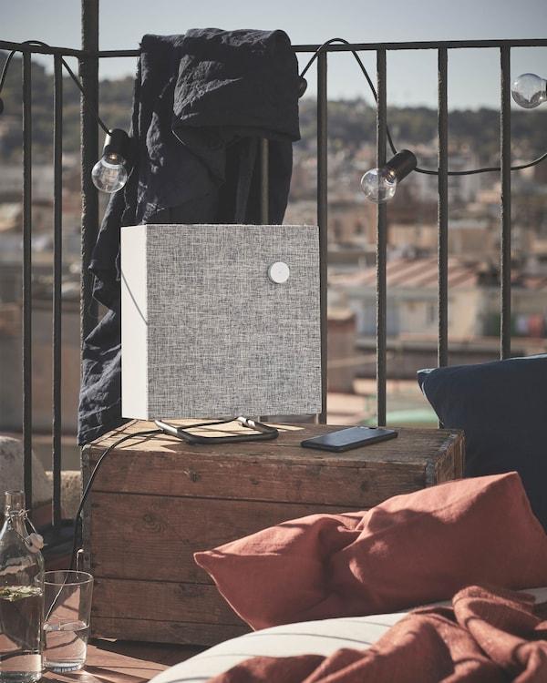 ENEBY luidsprekers op een zomers balkon. Ze zijn verkrijgbaar in twee maten en kleuren en passen in KALLAX en EKET kasten.