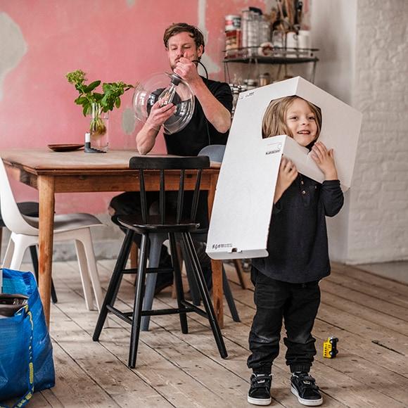 Enfant avec carton sur la tête dans une salle à manger avec un homme assis à table