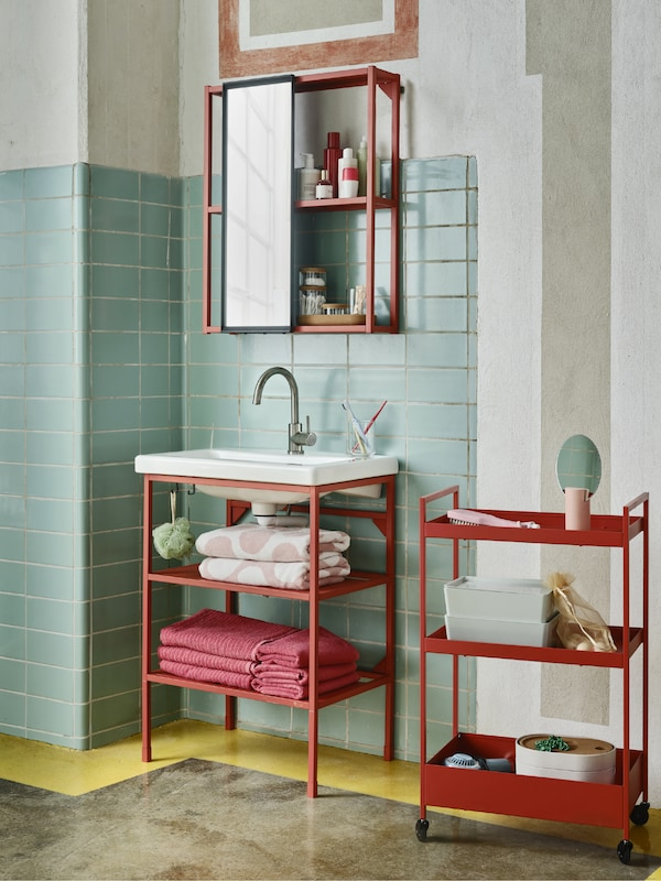 ENHET wash-basin stand and overhead storage in red-orange with an anthracite/grey mirror in a colourful bathroom.